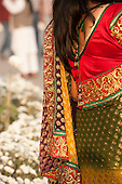 Delhi, India. A well-dressed Indian  woman from the back with brightly coloured sumptuous red, gold and green embroidered clothes.