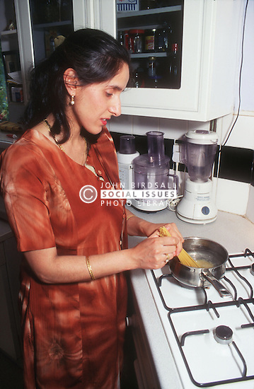 Woman standing next to oven in kitchen cooking spaghetti,