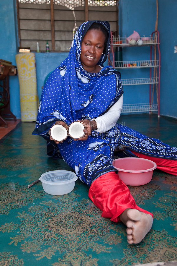 Jambiani, Zanzibar, Tanzania.  Woman Preparing to Make Coconut Milk.  She has just opened the coconut.  She wears a nose-pin in her left nostril.