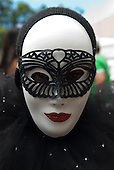 Rio de Janeiro, Brazil. Man wearing white female carnival mask with red glitter lips and black glitter mask.