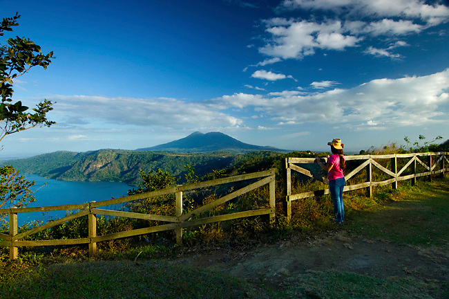 Tourist standing at the mirador or lookout admiring the stunning views of the Laguna de Apoyo, an extinct volcanic crater, and the Mombacho Volcano.