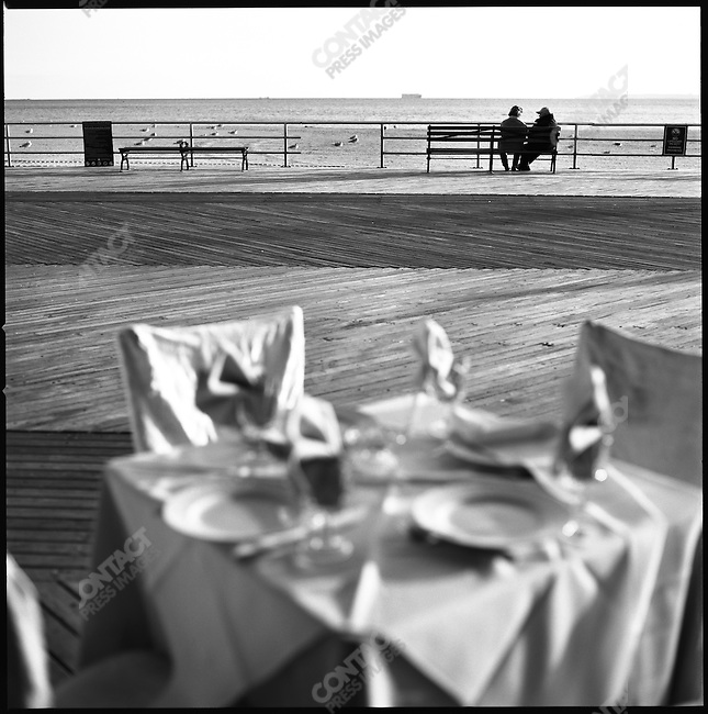 A couple sat on a bench on the boardwalk at Brighton Beach as table set for lunch stood vacant in front of a restaurant. New York City, New York, November 11, 2008
