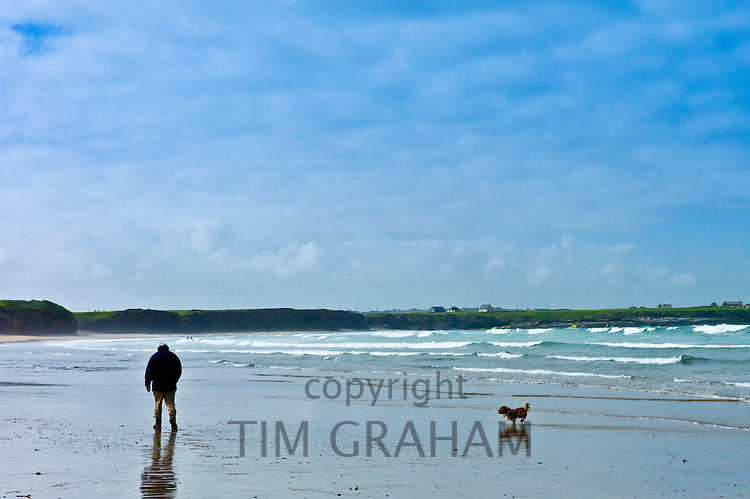 One man and his dog, Sheltie cross Corgi, stroll the beach at Spanish Point, County Clare, West Coast of Ireland