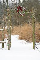 63821-19401 Rustic fence and arbor with holiday wreath & lights near prairie in winter, Marion Co.  IL