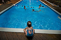 Girl (4-5) watches other children play in pool