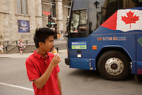 Montreal (Qc) CANADA - August 19 2009 - model released photo - asian (Filipino) male teen eating ice cream in front of Notre-Dame Basilica in Old-Montreal