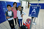 Dayanara Lopez and her children Josue Isaac and Genesis pose in the Greyhound Bus Station in San Antonio, Texas, on December 3, 2015. Lopez and her children, along with two teenage nephews, fled Honduras in October 2015 because of domestic violence and threats and assaults against her nephews from gangs. After requesting political asylum in the United States, they were held for several days by immigration officials and then released. The nephews were turned over to their mother, who already lived in the U.S. Lopez and her children stayed at first in a shelter run by the Refugee and Immigrant Center for Education and Legal Services (RAICES) and supported by a coalition of San Antonio churches. They then traveled by bus to another location in the U.S. while they await a final decision on their asylum petition.