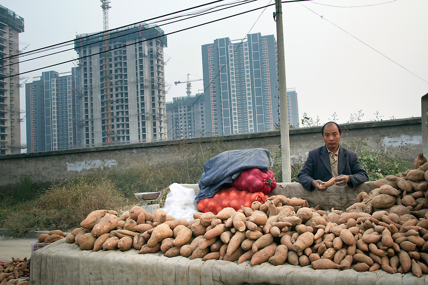 A farmer sells sweet potatoes next to the construction site of a new apartment complex in the newly developed area of Tongzhou on the outskirts of Beijing,