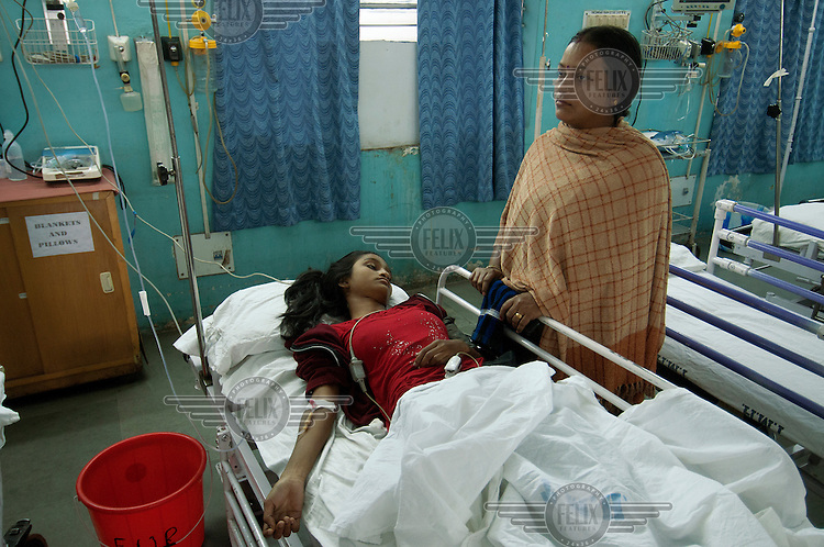 A woman stands over her daughter's bed in the out patient department of the Tata Main Hospital.