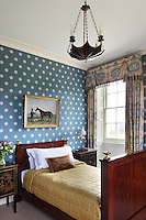A small bedroom with fringed curtains and a blue wallpaper with stylised white snowfakes