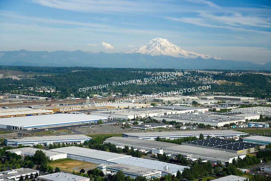 An aerial photo looking southwest from above the Kent Valley industrial area in south King County, south of Seattle, to a looming snow-capped Mount Rainier in the far distance.  In the event of a volcanic eruption, this low-lying area would be at risk of massive flooding and mudflows triggered by rapidly melting glaciers.  Topping out at just over 14,000 feet, Rainier last erupted roughly 350 years ago.
