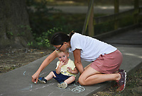 Nataliya Chapovska of Bentonville (right) makes chalk art with Anton Krapivin, 1, Monday, July 27, 2020 at Gibson Park in Bentonville. Nataliya Chapovska and Fennalia Carle find a new park for their kids to visit every day. Carle likes Gibson Park because they have shade in the mornings, the time when they like to meet. Gibson Check out nwaonline.com/200728Daily/ for today's photo gallery. <br /> (NWA Democrat-Gazette/Charlie Kaijo)