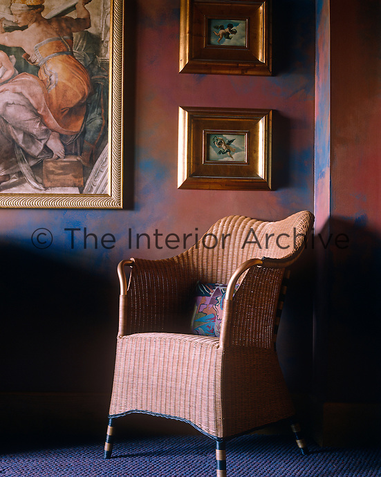A bronze-painted Lloyd Loom chair stands in a corner of the living room the walls of which have been painted a mixture of blue and terracotta creating a metallic effect