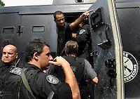 Policemen prepare to participate in an operation at Vila Cruzeiro slum, Rio de Janeiro, Brazil, November 25, 2010. Authorities in Rio de Janeiro try to control a fourth day of violence apparently orchestrated by drug gang members who have attacked police stations and burned cars in Rio de Janeiro city as protest by traffickers after being forced from their turf by police occupations of more than a dozen slums in the past two years..(Austral Foto/Renzo Gostoli)