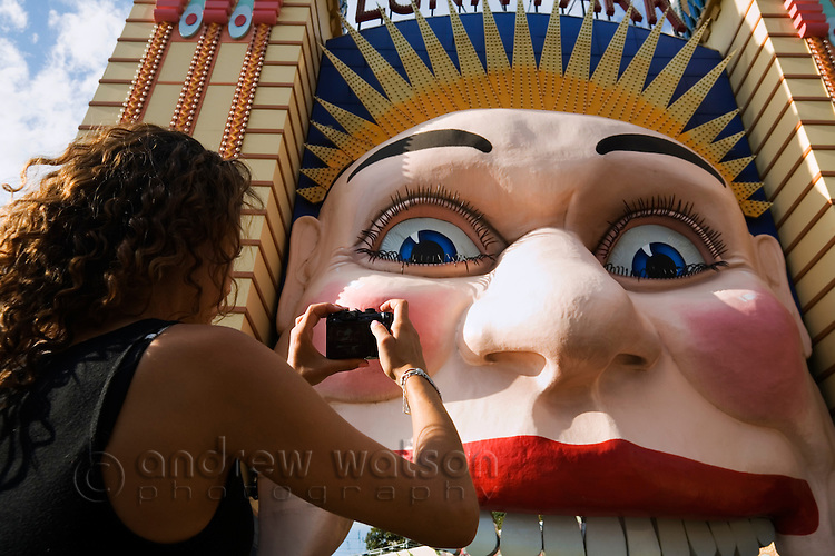 A woman photographs the smiling face of Luna Park on Sydney's north shore.  Sydney, New South Wales, AUSTRALIA.