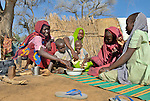 Fatna eats with her children in a camp for internally displaced persons outside Kubum, in South Darfur.