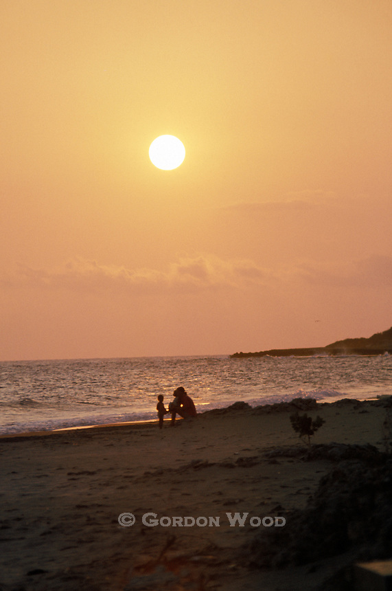Mother and Children on south coast beach in Jamaica at Sunset
