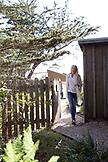 USA, California, Big Sur, Esalen, woman walks through a gate next to the Little Wooden Yurt at the Esalen Institute