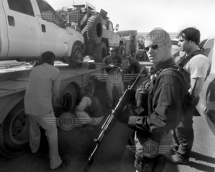 Private security operators Cory Koroituku (left),  Mark Richards and Steve Grant from the British company ArmorGroup guard drivers replacing a punctured wheel on one of their convoy's trucks near Al Asad air base on October 17, 2006.  The coalition forces and civilian administration in Iraq depend heavily on thousands of controversial security contractors to support their reconstruction efforts and military operations.