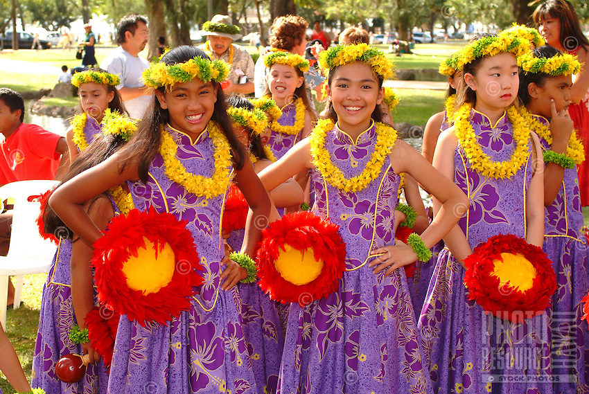 Young girlsgetting ready to dance a hula with uliuli, feathered gourd rattles, and leis in May day performance at the Kapiolani bandstand
