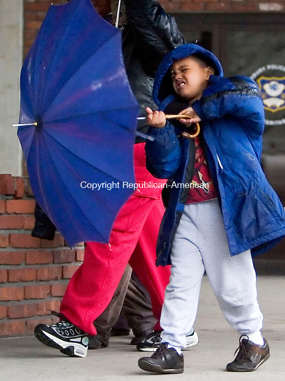 WATERBURY, CT- 15 APRIL 07- 041507JT06- <br /> Miguel Ortiz, 5, plays with his umbrella as he walks under a covered area on Bank Street in Waterbury on Sunday as a Nor'easter blew through the area with strong winds and excessive rain. <br /> Josalee Thrift Republican-American