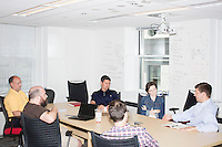 John Fawcett, the CEO and co-founder of Quantopian, (in light blue shirt) leads a meeting on future business strategy with his executive team in the offices of Quantopian in the Downtown Crossing area of Boston, Mass., on Wed., June 1, 2016. A couple of participants took part in the meeting remotely via a webcam on one of the laptops in the center of the room. Quantopian is a Boston-based start-up that provides a platform for building, testing, and executing stock trading algorithms.