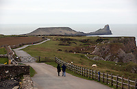 Pictured: A couple walking on the path that leads to Worm's Head. Monday 17 March 2014<br />