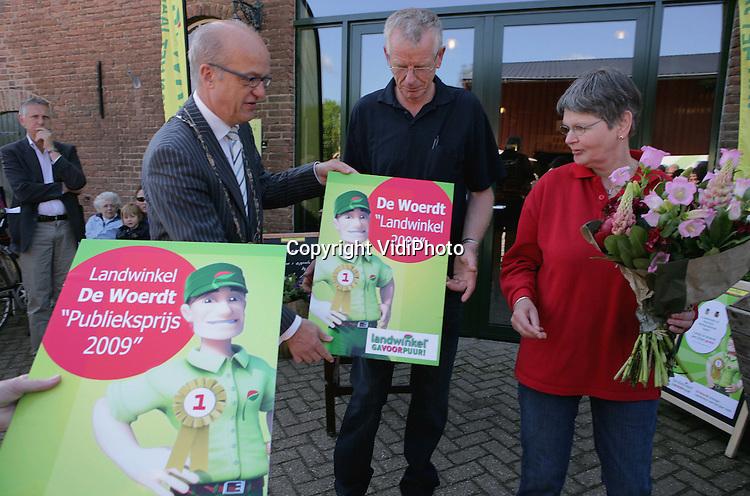 Foto: VidiPhoto..RESSEN - De beste landwinkel van Nederland staat in Ressen bij Nijmegen. Landwinkel De Woerdt is zaterdag uitgeroepen tot beste landwinkel van 2009. Het bedrijf van de familie Van Olst is gekozen uit 75 agrarische ondernemingen die een winkel hebben bij hun boerderij of boomgaard. De Woerdt heeft eveneens de publieksprijs gewonnen. Al die winkels zijn aangesloten bij de landelijke organisatie Landwinkel. Andere genomineerden waren De Zandroos uit Afferden, De Koningshoeve uit Klaaswaal en Westerstrate uit Middelburg. De landwinkels in Nederland, met vooral Nederlandse producten, trekken steeds meer publiek ten koste van de supermarkten. Foto: Burgemeester Harry de Vries van Lingewaard reikt de prijs uit aan Nico van Olst.