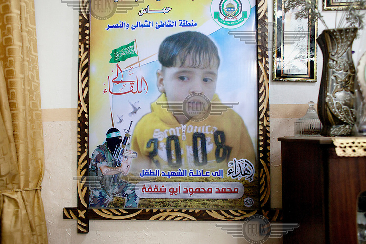 A 'Martyrs' poster showing the dead son of Mahmood Abu Shaqfa. On 7 July 2014, Israeli forces launched a large-scale military operation ('Pillar of Defense') in the Gaza Strip). The operation lasted 51 days and resulted in 2,145 deaths and 11,231 injuries among the Palestinian population. The vast majority of the serious casualties have complex orthopaedic injuries that the Palestinian Ministry of Health is ill-equiped to manage. DFID/UK Aid is funding NHS Doctors, deployed through the UK's Rapid Response Facility's funding, to work alongside Medical Aid for Palestinians (MAP) in providing post conflict surgery at Gaza's Shifa Hospital. The NHS doctors (through the charity Ideals) volunteer to visit Gaza in their spare time and work alongside their Palestinian colleagues. <br /> <br /> 20 year old Mahmood Abu Shaqfa&nbsp;sustained serious injuries during the offensive. In the same attack his eight year old son sustained mortal injuries. Abu Shaqfa describes the events: 'It was the first day of Eid and we were sitting, all of us, my kids, my uncle and my cousins, outside in the street and the kids were on the swings and then suddenly a rocket hit us directly. Before I entered a coma I remember my little child Mohammed sitting in my lap, looking up at me, he had internal injuries but I didn't know it at the time, for just a few seconds before I passed out I thought he was ok. I saw my uncle's hands bleeding and my cousin lying in the street full of blood. And then I fell in a coma and woke up after eight days. When I woke up I was in Shifa hospital, when I opened my eyes I asked about Mohammed straight away as I remembered him in my lap, they told me he was ok. Then I looked at my leg and hand because I wanted to make sure I didn't lose them, then, I fell back into a coma. Then they operated on me to remove all the shrapnel from my body. <br /> <br /> I didn't know about all these martyrs, they didn't want to tell me, I found out my son was dead eight days later. I knew something was strange bec