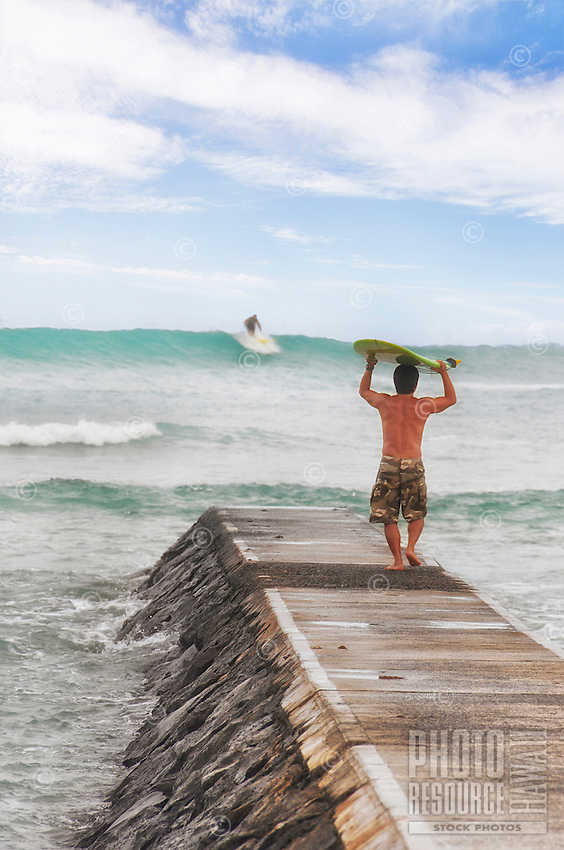 A young man carries his surfboard on the jetty to the water while another surfer rides an offshore wave, Waikiki, O'ahu.