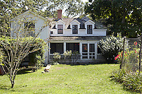 The rear of the property shows the clapboard exterior and traditional porch of properties in this part of America
