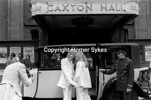 Caxton Hall, Westminster London. Londons main register office until 1979. White wedding, his and her uni sex clothes, she is wearing a trouser suit. rather than a wedding dress, very fashionable at that time. 1970s London ..He is Michael Stephens, I think a well know hairdresser of the time. ..