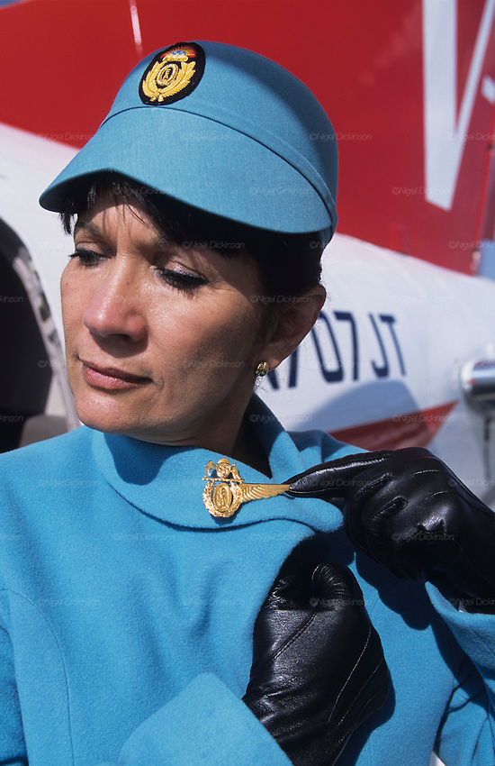 "Crew of John Travolta's jumbo jet. A  stewardess wearing Chanel designed uniforms..John Travolta is pilot of his very own jumbo jet, a 1964 Boeing 707-100 series. In 2003, John Travolta flew his jumbo jet around the world, in partnership with Quantas, to rekindle confidence in commercial aviation, and to remind us that elegance and style are a part of flying. The crew are dressed in tailor made authentic uniforms from the Quantas museum. The men's uniforms are styled on British Naval uniforms and the ladies' designed by Chanel. His jumbo jet sports a personalised number plate N707JT which speaks for itself. The aircraft is named ""Jett Clipper Ella"" dedicated to his son and daughter. This jumbo together with his other aircraft are housed in purpose built hangars at his home in Florida, USA."