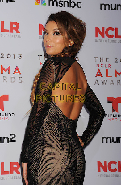 Eva Longoria<br /> 2013 NCLR ALMA Awards held at Pasadena Civic Auditorium, Pasadena, California, USA.<br /> 27th September 2013<br /> pressroom press room half length black sheer long sleeve dress looking over shoulder side cut out away backless <br /> CAP/ROT/TM<br /> &copy;Tony Michaels/Roth Stock/Capital Pictures