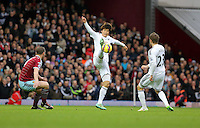 Sunday 07 December 2014<br /> Pictured: Ki Sung Yueng of Swansea (C) shoots the ball away from Kevin Nolan  of West Ham (L)  <br /> Re: Premier League West Ham United v Swansea City FC at Boleyn Ground, London, UK.