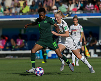 GRENOBLE, FRANCE - JUNE 22: Halimatu Ayinde #18 of the Nigerian National Team passes the ball  as Lea Schueller #7 of the German National Team closes during a game between Nigeria and Germany at Stade des Alpes on June 22, 2019 in Grenoble, France.