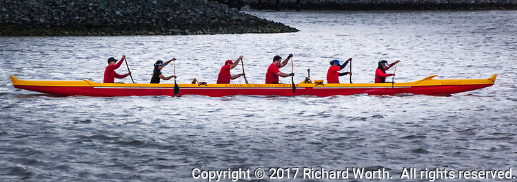 Six members of the Kaimanu Outrigger Canoe Club, a mix of men and women, guide their craft around the waters at the San Leandro Marina Park on a chilly springtime afternoon.
