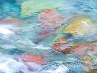 Water rushing over colorful river rocks at Rising Sun Creek, Glacier National Park