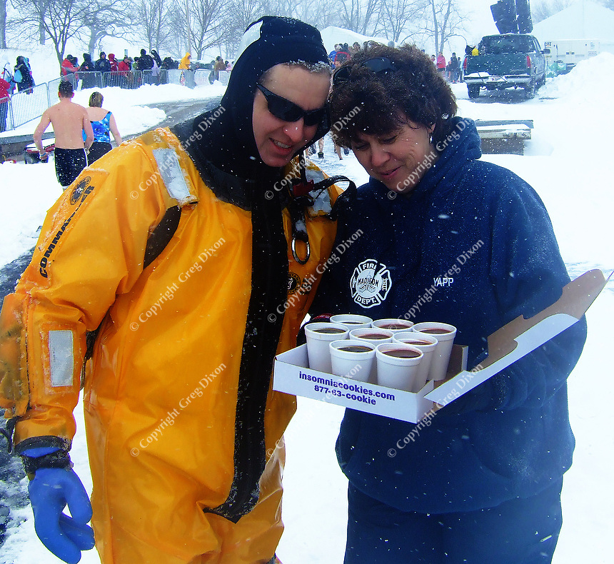 Madison Fire Department worker Joanne Yapp rescues Matt Powers with some hot coffee at the Polar Plunge at Olin Park on Saturday morning, 2/21/09