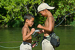 Six- and eight-year-old brothers choose a fly to fool bluegill and smallmouth bass on the James River, Missouri.