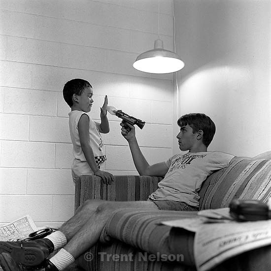 Bob Walter pointing gun at little kid, who is holding his hand in front of the gun.<br />