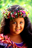 A beautiful smiling young Hawaiian girl dressed in a purple muu muu and wearing a haku lei (floral headpiece) and plumeria lei stands in front of muted green foliage.