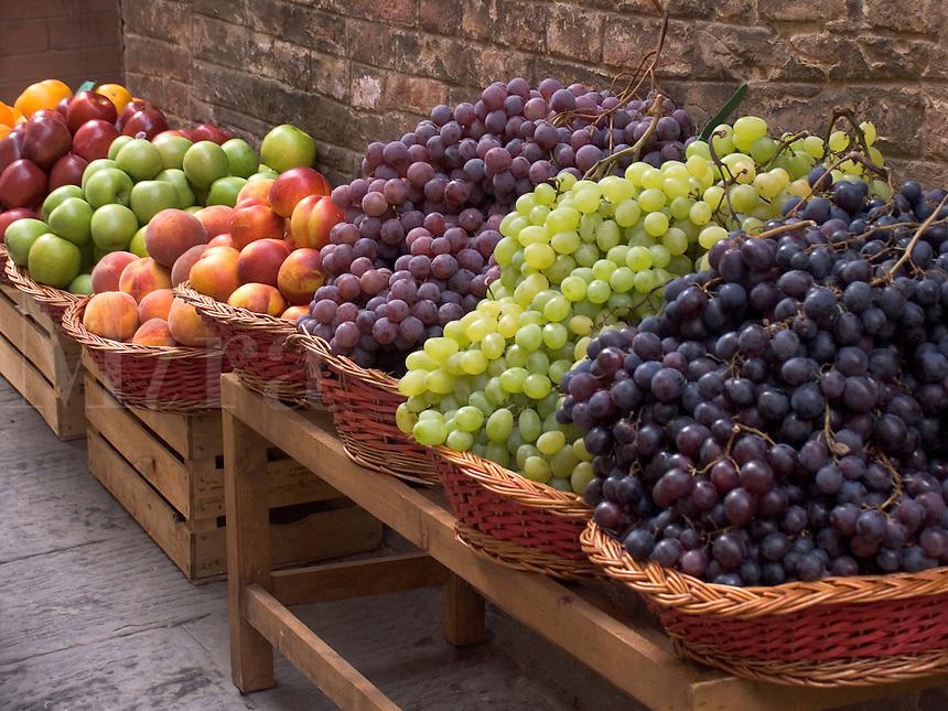 Fresh grapes in wicker baskets outside shop in Siena, Ital