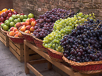 Fresh grapes in wicker baskets outside shop in Siena, Ital