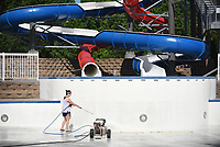 Claire Sanchez, manager of the Springdale Aquatics Center, uses a power washer to clean the sides and bottom of the shallow wave pool Monday, May 18, 2020, at the center in Springdale. The city has announced Monday, June 8, as the opening date for this year. Check out nwaonline.com/200519Daily/ and nwadg.com/photos for a photo gallery.<br /> (NWA Democrat-Gazette/David Gottschalk)