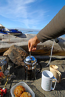 POV point of view shot of arm pushing the plunger of French Press coffee pot in a beach kitchen, Olympic National Park, Coastal Strip, Olympic National Park, WA.