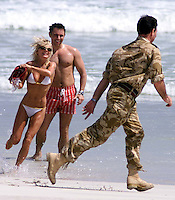 Geri Halliwell throws water over  her Armed Forces escort Wing Commander Mark Smith on the beach  at the Hilton Hotel in Salalah ,Oman .Tonight Saturday 6th October 2001 Geri will be performed a live concert for the Armed forces at a camp in the middle of the Oman desert . Photo By Andrew Parsons/ Press Association