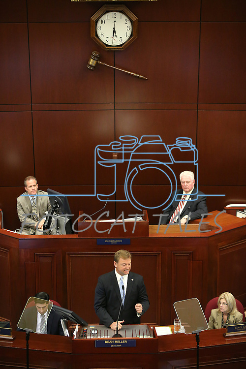 Nevada Lt. Gov. Mark Hutchison, left rear, and Assembly Speaker John Hambrick, R-Las Vegas, right rear, listen as U.S. Sen. Dean Heller delivers his address at the Legislative Building in Carson City, Nev., on Monday, April 6, 2015. <br /> Photo by Cathleen Allison