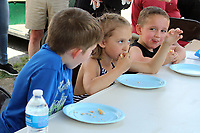 MEGAN DAVIS/MCDONALD COUNTY PRESS Rival competitors survey Isabelle Wittenmeyer as she intently finishes her donut and claims victory during the Donut Eating Contest on Saturday. Wittenmeyer finished her donut in 1 minute, 30 seconds.