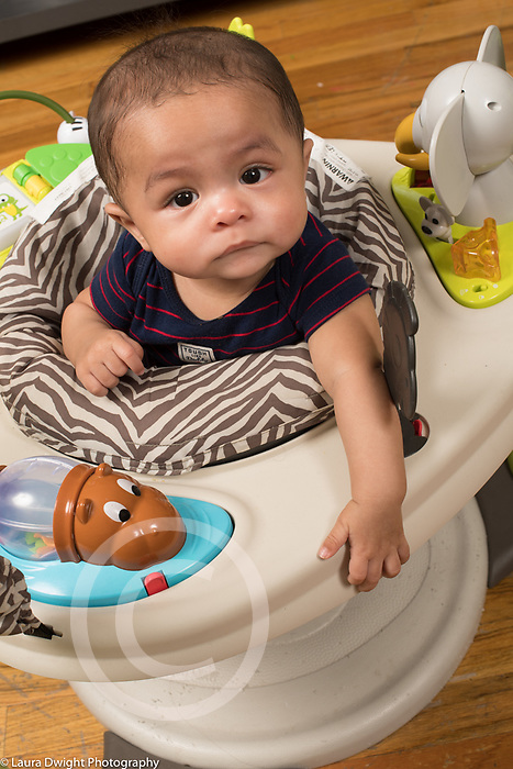 """6 month old baby boy closeup in stationary """"walker"""" looking up expression uncertain, concerned"""